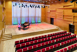 Concert hall auditorium, with rows of seats, grand piano. Heino Eller's Tartu Music School in Estonia. Large window covered curtain.