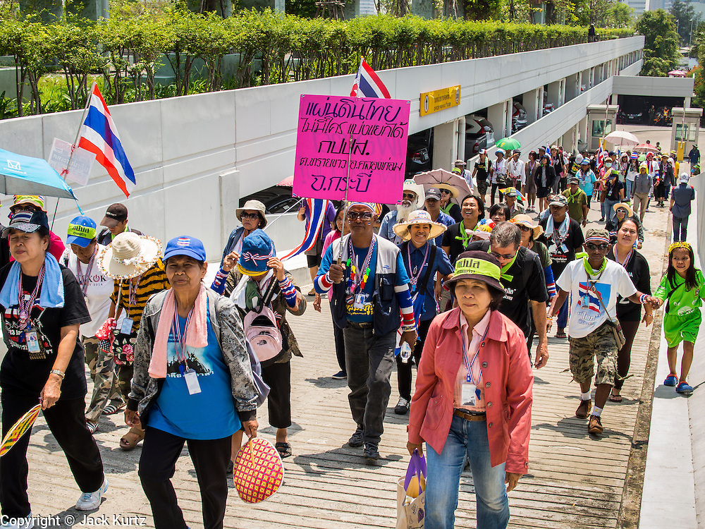 "08 APRIL 2014 - BANGKOK, THAILAND: Anti-government protestors march into the Ministry of Justice compound in Bangkok. Several hundred anti-government protestors led by Suthep Thaugsuban went to the Ministry of Justice in Bangkok Tuesday. Suthep and the protestors met with representatives of the Ministry of Justice and expressed their belief that Thai politics need to be reformed and that corruption needed to be ""seriously tackled."" The protestors returned to their main protest site in Lumpini Park in central Bangkok after the meeting.    PHOTO BY JACK KURTZ"