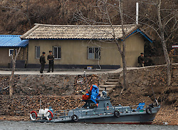 North Korea soldiers and a military boat are seen along the North Korean bank of the Yalu River near the town of Sinuiji across the Chinese city of Dandong, Liaoning Province, China on 06 April 2013. North Korean leader Kim Jong-un has ordered the country's military to increase artillery production, a televised report out of Pyongyang showed 06 April.