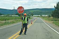 Public road worker standing in the road stopping traffic