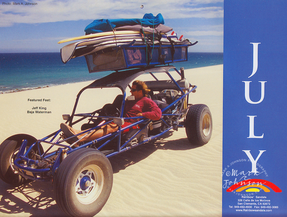 Jeff King in his dune buggy checking the surf in Baja. Rainbow Sandals calendar photo