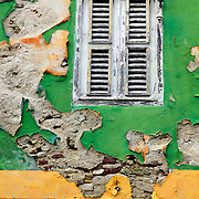 SHOT 3/17/11 7:59:17 AM - A decaying and crumbling wall around a door and window in the Scharloo section of Willemstad. Willemstad is the capital city of Curaçao, an island in the southern Caribbean Sea that forms a constituent country of the Kingdom of the Netherlands. Formerly the capital of the Netherlands Antilles prior to its dissolution in 2010, it has an estimated population of 140,000. The historic centre of the city consists of two quarters: Punda and Otrobanda. The city center of Willemstad boasts an array of colonial architecture that is influenced by Dutch styles. The city center, with its peculiar architecture and beautiful harbour entry, has been made a UNESCO world heritage site. (Photo by Marc Piscotty / © 2010)
