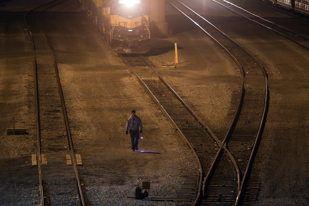 The conductor on an Iowa, Chicago & Eastern train walks through the yard to line the switches for his train as they prepare to put the train away in Canadian Pacific's giant Bensenville classification yard.