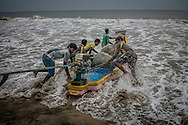Artisanal fishermen launch a kattumaram* boat, which means &quot;logs bound together&quot; in Tamil, from the beach in Pondicherry.  Their kattumarm is an updated version of the traditional raft used for centuries by fishermen, with the addition of an engine, for fishing close to shore.  Fish hauls, however, have decreased due to overfishing.  Conservation India conducted a study in 2010 85% of all artisanal fishermen surveyed had experienced declines in fish catch.  Meanwhile most trawler fishermen admitted to not obeying laws which prevent them from fishing within 3 nautical miles (5.6 km) of shore putting them in direct competition with artisanal fishermen.  Pondicherry, India.<br /> <br /> *Kattumaram is the origin of the word, catamaran.