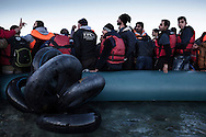 Arrived on the shores of Lesbos near Mytilene airport, refugees from Afghanistan and Syria wait to disembark their rubber boat under guidance of helpers to avoid a frantic stampede, Greece on 08 January, 2016. Lesbos, the Greek vacation island in the Aegean Sea between Turkey and Greece, faces massive refugee flows from the Middle East countries.