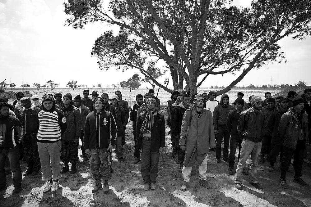 Des nouvelles recrues prêtes à combattre sont au garde-à-vous, le 02 avril 2011, dans la banlieue de Benghasi, après avoir très rapidement appris le maniement des armes légères.