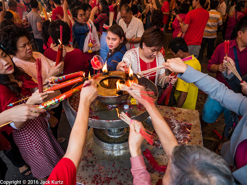 "08 FEBRUARY 2016 - BANGKOK, THAILAND:  People make merit for Chinese New Year by lighting candles and incense at Wat Mangon Kamlawat, the largest Mahayana (Chinese) Buddhist temple in Bangkok during the celebration of the Lunar New Year. Chinese New Year is also called Lunar New Year or Tet (in Vietnamese communities). This year is the ""Year of the Monkey."" Thailand has the largest overseas Chinese population in the world; about 14 percent of Thais are of Chinese ancestry and some Chinese holidays, especially Chinese New Year, are widely celebrated in Thailand.      PHOTO BY JACK KURTZ"