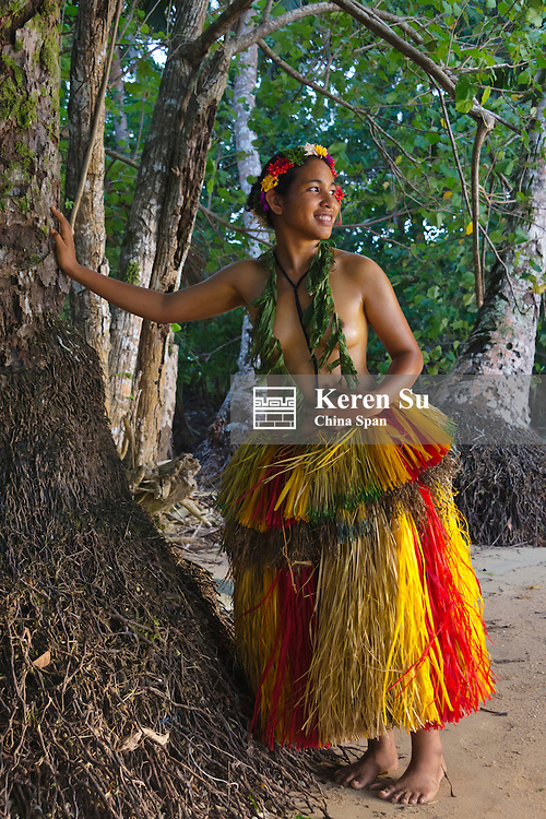 Yapese girl in grass skirt standing by a tree, Yap Island, Federated States of Micronesia