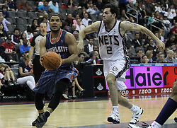 Apr 11; Newark, NJ, USA; Charlotte Bobcats point guard D.J. Augustin (14) drives past New Jersey Nets point guard Jordan Farmar (2) during the second half at the Prudential Center. The Bobcats defeated the Nets 105-103.