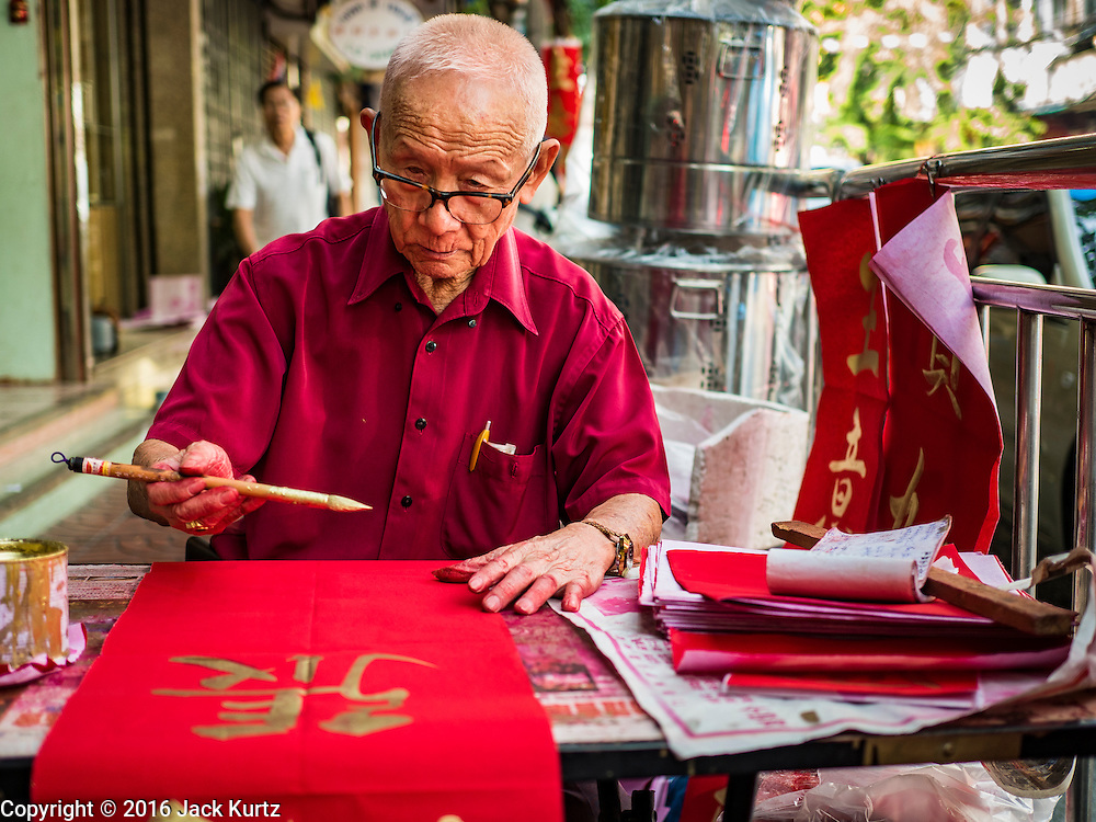 """03 FEBRUARY 2016 - BANGKOK, THAILAND:  A traditional Chinese calligrapher writes out New Year's greetings before Chinese New Year for customers on Chareon Krung Road in Bangkok's Chinatown. Thailand has the largest overseas Chinese population in the world; about 14 percent of Thais are of Chinese ancestry and some Chinese holidays, especially Chinese New Year, are widely celebrated in Thailand. Chinese New Year, also called Lunar New Year or Tet (in Vietnamese communities) starts Monday February 8. The coming year will be the """"Year of the Monkey.""""            PHOTO BY JACK KURTZ"""