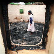 A woman searches the remains of her grandmother in a burned out roundaval hut in the hamlet of Shoboshobane, on the KwaZulu/Natal South Coast.  On Christmas Day, the ANC village was attacked by Inkatha neighbours killing more than 20 residents, and driving the rest into refugee camps.  December 26th, 1995.