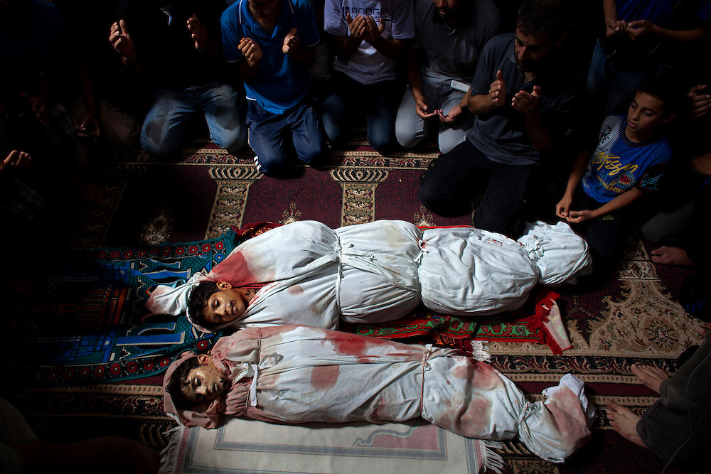 Family members pray in the mosque in Sajeria , Gaza by the  bodies of Amir,15, Mustafa Arief and Mohammed during their funeral in Sajeria ,Gaza July 9,2014. The brothers were killed together  near their home allegedly by an Israeli drone in the  Sajeria neighborhood on the eastern outskirts of Gaza City, Gaza .