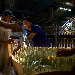 "Workers do quality control and ready bottles to hold Murree beer in Rawalpindi, Pakistan, Sept. 12, 2007. With a limited market in Islamic Pakistan, the company is looking for opportunities abroad. Soon the brewery's beer will be sold in Britain and India with the advertising slogan: ""Have a Murree with your curry."" The almost 150 year old Murree Brewery is preparing to bring the Muslim world's first 20 year old single malt whisky to the market. However, they can only sell to non-Muslims, who comprise 3 percent of Pakistan's population."