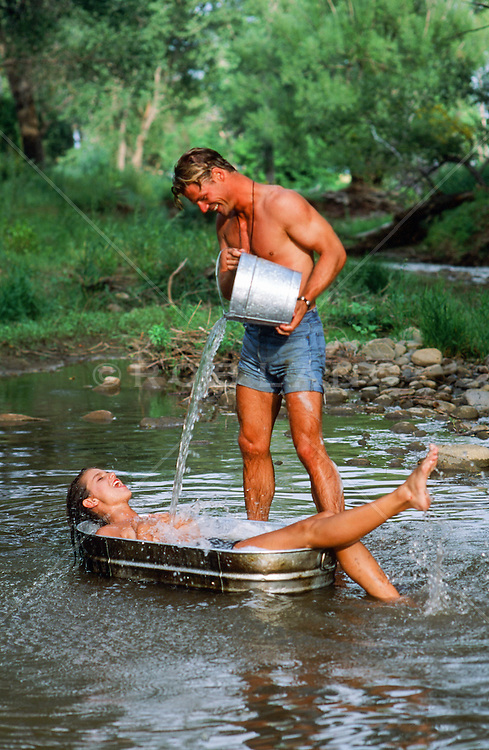 man pouring water from a bucket on a woman in a metal bathtub in a stream