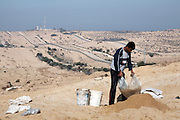 A boy sieves sand for gravel beside Gaza's northern border with Israel. Under the blockade there is a severe lack of building materials in Gaza.