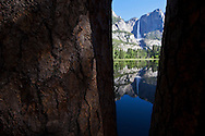 Yosemite Falls reflected in Sentinel Meadow flooded by the Merced River seen between Ponderosa Pine trees - Yosemite National Park, California