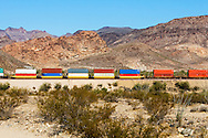 A train of international ocean container hustles eastward on the BNSF mainline through Arizona. All logos have been removed.
