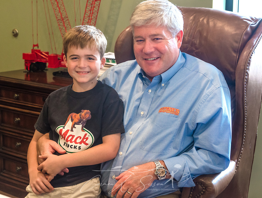 "Pat Barber poses with his son, James Barber, who dropped by Superior Transportation to visit and ""work with dad,"" Sept. 30, 2015, in North Charleston, South Carolina. Barber started the company in 1998. James, 6, is already showing a big interest in the company and its Mack trucks, and Barber says he hopes he will follow in his footsteps and carry on the family legacy.  (Photo by Carmen K. Sisson/Cloudybright)"