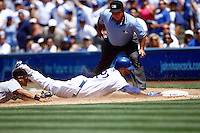9 May 2009: #27 Matt Kemp slides into first base in the 8th inning during  the MLB Los Angeles Dodgers 8-0 shut out over the San Francisco Giants in game 32 of the National League regular season. Weather was sunny and 73', they played infront of 41,425 fans on Saturday.  First base umpire Charlie Reliford watches as Emmanuel Burriss gets cannot tag him out before he reaches the bag.