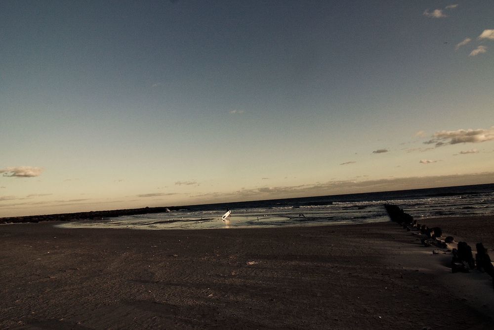 A surfer goes into the water at 91 st. surf break, Rockaway Beach, Queens, NY.