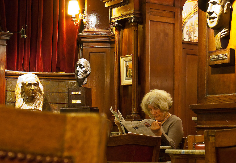 A woman reads a newspaper at Cafe Tortini in Buenos Aires, Argentina. Cafe Tortoni, which opened in 1858, has always been a meeting place for the local intellectuals and celebrities.