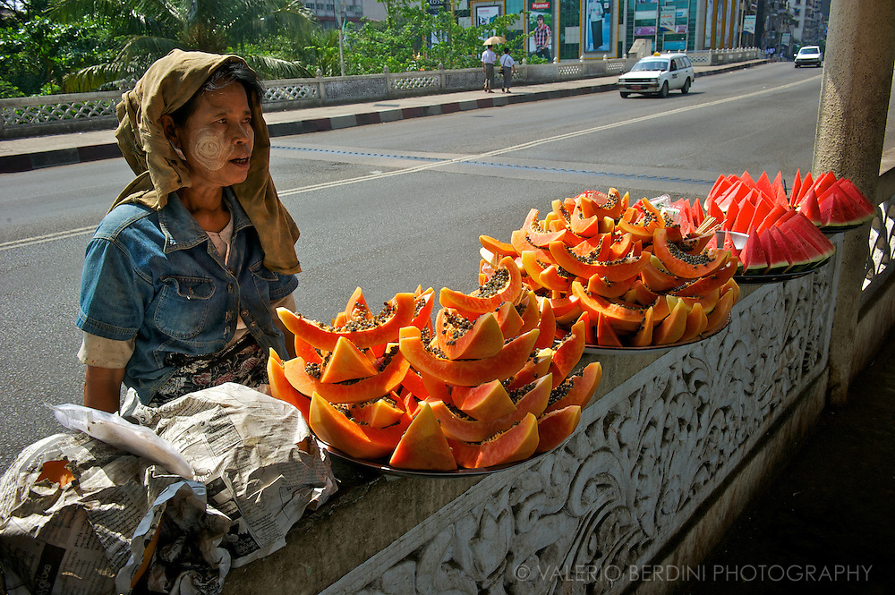 A woman with the head covered and the refreshing thanaka make-up stands on the bridge over the central railway station selling papaya and watermelon slices to commuters on a torrid April day.