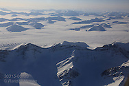 Aerial view of snowy mountain wilderness in April on flight from Longyearbyen to Ny-Alesund; Svalbard, Norway.