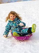 Annika Berge, 3, sleds down the hill at Rangeview Park on Saturday evening.