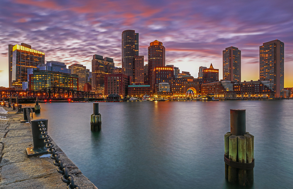Boston Harbor skyline photography from New England Photography Guild member and award winning fine art photographer Juergen Roth showing Boston Financial Waterfront District landmarks such as One International Place, Boston Harbor Hotel, Independence Wharf, Department of Homeland Security building, and other structures along Rowes Wharf photographed on a beautiful winter sunset evening. The last light was painting the cloudscape in fire red hues and the long exposure time ensured the intentional blurry cloud movement. <br /> <br /> Skyline photos of Boston are available as museum quality photo prints, canvas prints, wood prints, acrylic prints or metal prints. Fine art prints may be framed and matted to the individual liking and decorating needs:<br /> <br /> http://juergen-roth.pixels.com/featured/boston-harbor-and-financial-waterfront-district-skyline-juergen-roth.html<br /> <br /> All digital Boston skyline photography images are available for photo image licensing at www.RothGalleries.com. Please contact me direct with any questions or request.<br /> <br /> Good light and happy photo making!<br /> <br /> My best,<br /> <br /> Juergen<br /> Prints: http://www.rothgalleries.com<br /> Photo Blog: http://whereintheworldisjuergen.blogspot.com<br /> Instagram: https://www.instagram.com/rothgalleries<br /> Twitter: https://twitter.com/naturefineart