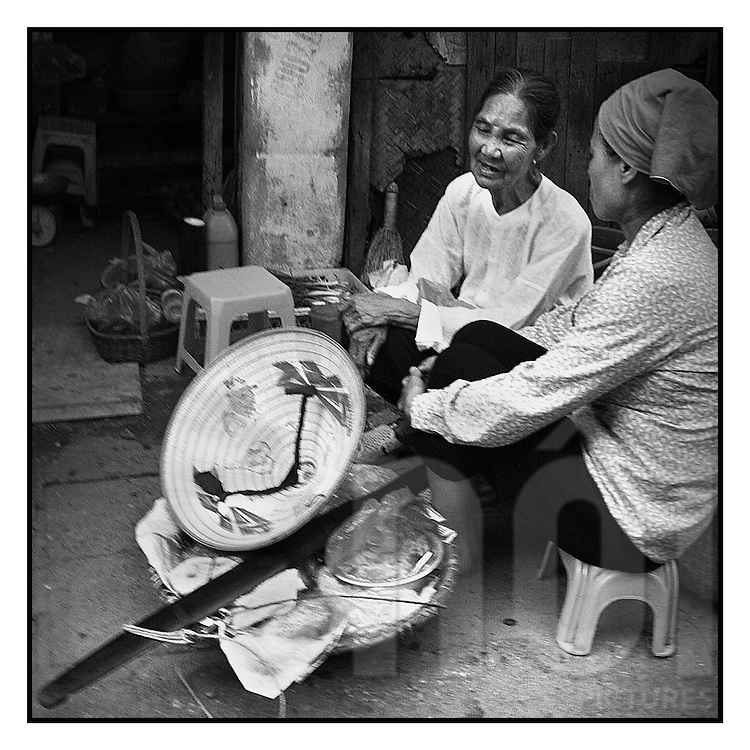 Black and white picture of old women talking in the street.