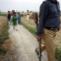 Guards lead the way as Mukhtar Mai and family members walk through a field after visiting an aunt she hadn't seen for four years, Meerwala, Pakistan, April 28, 2005. Mai, 33, went against the Pakistani tradition of committing suicide when she brought charges against the men who gang raped her nearly three years ago.
