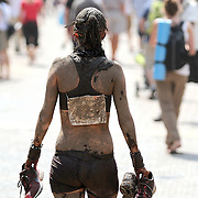 SHOT 6/4/11 3:24:44 PM - Elizabeth Tapper of Denver, Co. walks the streets of Vail, Co. covered in mud after the Mud Run at the 10th Annual Teva Mountain Games in Vail, Co. Professional and amateur outdoor adventure athletes from the Vail Valley and around the world will converge upon the mountains and rivers of Vail to compete in eight sports and 23 disciplines including: x-country, freeride, slopestyle and road cycling, freestyle, 8-Ball, sprint and extreme kayaking, raft cross, World Cup Bouldering, stand up paddle sprint and surf cross, as well as trail, mud and road running, dog comps and the GNC Ultimate Mountain Challenge.. (Photo by Marc Piscotty / © 2010)
