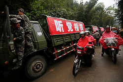 Chinese soldiers in supply trucks and motorcyclists wait for a road to be cleared off a fallen boulder in Taiping town of Lushan County, Sichuan Province, China, 23 April 2013. Landslides and fallen rocks block vital roads carrying supplies to remote towns and villages affected by the earthquake. The Lushan Earthquake in Sichuan Province on 20 April 2013 resulted in 186 people dead, 21 missing, 11248 injured. About 1.72 million people were affected by the quake, while an initial estimate by the International Red Cross on Saturday put the number needing emergency shelter, water and food at 120,000. The China Earthquake Administration (CEA) recorded a magnitude 7.0 earthquake, while the US Geological Survey said it had measured 6.9.