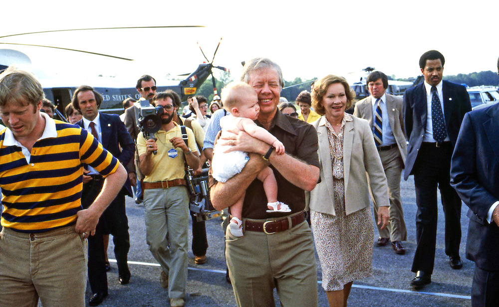President Jimmy Carter, holds grandchild accompanied by son Jack (left) and wife Rosalynn (right) in 1979. Carter had just landed on Marine One, the presidential helicopter. - To license this image, click on the shopping cart below -