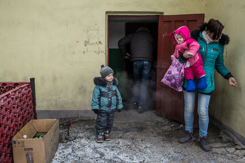 DONETSK, UKRAINE - JANUARY 29, 2015: Katerina Dynya, 22, right, returns with her son Nikita, 4, daughter Miroslava, 1, and husband, Aleksandr Dynya, 31,  to their apartment in the Petrovskyi district of Donetsk, Ukraine. The family has been living in an underground bomb shelter for the past several days but came home during a break in shelling to shower. CREDIT: Brendan Hoffman for The New York Times