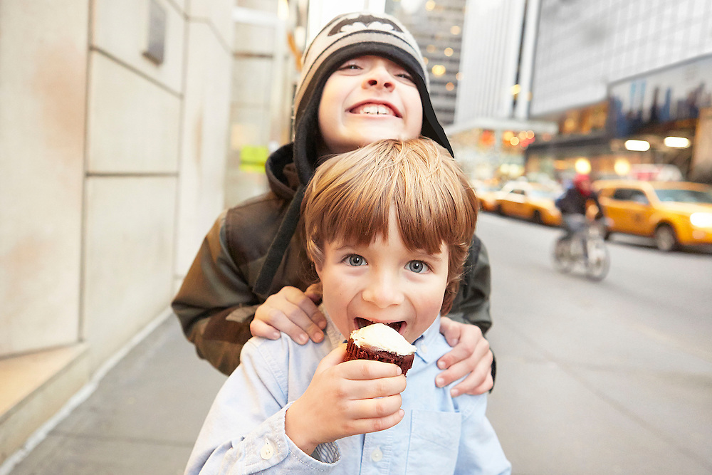 Lifestyle image of two children playing and having fun with one of the kids eating a cupcake
