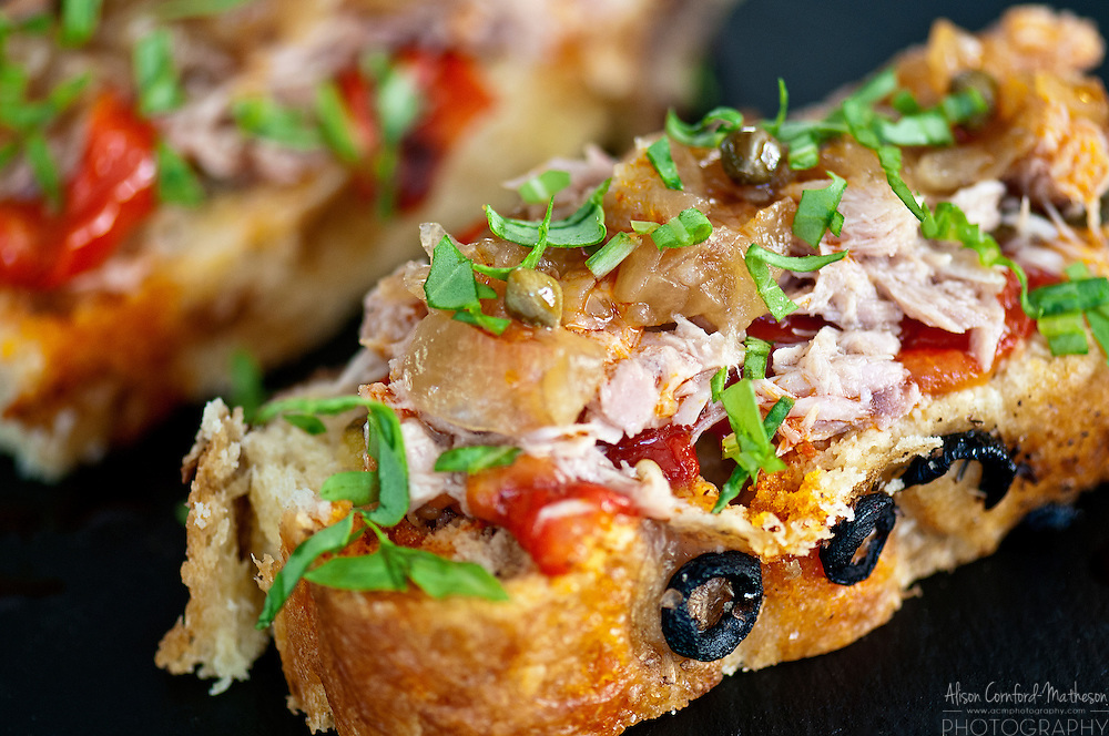 Open Faced sandwich with seafood and olives.
