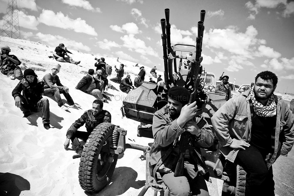 Des combattants rebelles se reposent et attendent les ordres, le 22 mars 2011 à une dizaine de kilomètres d'Aj Dabiya sur la ligne de front.