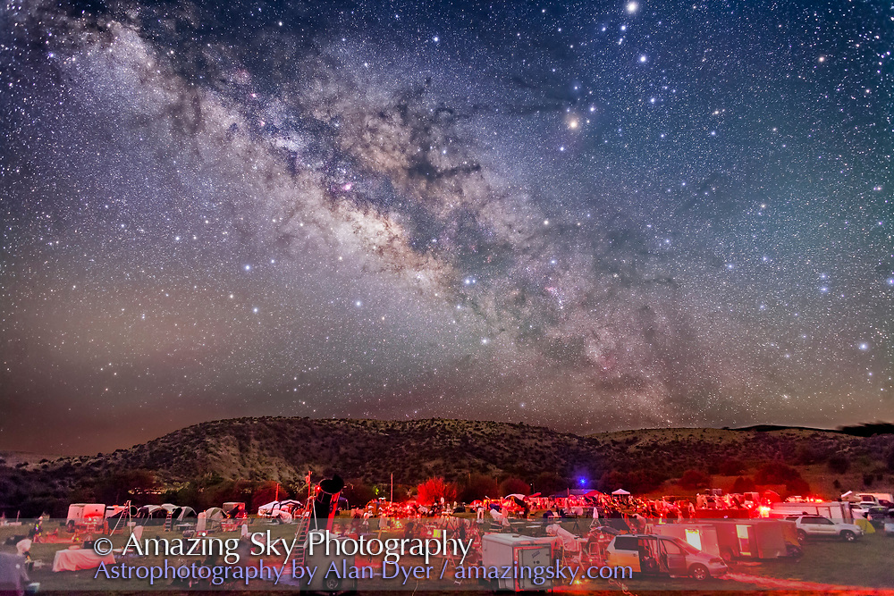 The galactic centre region of the Milky Way in Sagittarius and Scorpius, over the upper field of the Texas Star Party, near Fort Davis, Texas, May 13, 2015. About 600 people gather here each spring for a star party under very dark skies near the MacDonald Observatory. Sagittarius is left of centre and Scorpius is right of centre with the planet Saturn the bright object at the top edge right of centre. The dark lanes of the Dark Horse and Pipe Nebula areas lead from the Milky Way to the stars of Scorpius, including Antares. The semi-circular Corona Australis is just clearing the hilltop at left of centre.<br /> <br /> This is a composite of 5 x 3 minute exposures with the camera tracking the sky for more detail in the Milky Way without trailing. Each tracked exposure was at ISO 1600. The ground comes from 3 x 1.5-minute exposures at ISO 3200 taken immediately after the tracked exposures but with the drive turned off on the tracker. All are with the 24mm lens at f/2.8 and filter-modified Canon 5D MkII camera. The ground and sky layers were stacked and layered in Photoshop. The tracker was the Sky-Watcher Star Adventurer. High haze added the natural glows around the stars &mdash; no filter was employed here.