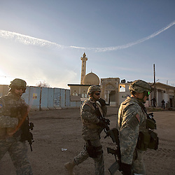 "Left to right, 1st Lt. David Musick, translator Mushtag ""Mitch"" Alleathe and Major Jonathan Fox, are seen entering the Four West Police Station to see new detainees caught by the Iraqi Police in Mosul, Iraq, Dec. 10, 2005. A police sniper perched atop the mosque helped catch members of an insurgent cell after they killed a member of an opposing political party. Members of the 1st Infantry, 17th Regiment, were helping Iraqi forces secure the area in preparation for Iraq's first post-Saddam parliamentary elections. The western sector is home to Mosul's primarily Sunni population, which has been resistant to the American presence in Iraq."