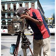 Portrait photographer with vintage large format camera, Havana, Cuba.