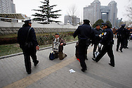 A Protester is approached by police after voicing his complaints and asking for justice outside of the Foreign Ministry  Beijing, China, Wednesday, Dec.10, 2008. Two dozen people held a bold protest using the 60th anniversary of the declaration of human rights to decry a myriad of alleged government abuses.