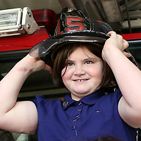 (Boston, MA - 4/15/15) Jane Richard, who lost her brother Martin and her leg in the Boston Marathon bombings, smiles as she tries on a fire helmet while visiting Boston Firefighters at the Back Bay fire station, Wednesday, April 15, 2015. Staff photo by Angela Rowlings.