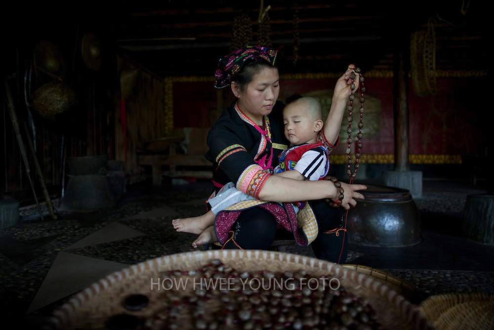 epa02689220 A Miao ethnic minority woman holds her child on her arms as she makes tourist souvenirs from rubber fruits in 'Bing Lang Gu' or the Areca Valley of Hainan Ganza Ridge Primitive Culture on the border of Sanya City and Baoting County of Hainan Province, China, 15 April 2011. Some major tourist attractions in Hainan are Li and Miao ethnic minority villages and the tropical jungle. Hainan, an island off the south coast known for its warm climate has been rapidly developed as the country's tourism hotspot.  EPA/HOW HWEE YOUNG