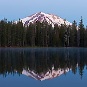 Lassen Peak, a 10,462 foot (3,189 meter) volcano in northern California, is reflected in Summit Lake just before sunrise. Lassen Peak is the southernmost volcano in the Cascade Range and last erupted from 1914-1917.