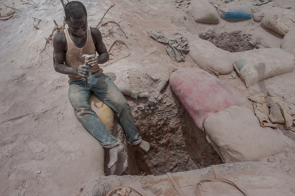 Nobsin, Burkina Faso - 13 May 2014: sat on the edge of a 25 meters mine shaft, a young man readies his forehead torch as he prepares to descend to dig for gold. In the around 700-800 artisanal sites around the country, there's no health and safety, no hard hats or harnesses, no protective masks, no lights and no decent ventilation system.