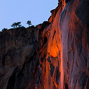 """Horsetail Fall, an ephemeral waterfall that plunges from the top of El Capitan in Yosemite National Park, California, is reddened by the setting sun. The waterfall, which flows only for a few weeks each year in late winter and early spring, drops a total of 2,130 feet (650 meters). Horsetail Fall is best known for its dramatic """"fire fall"""" effect, which if the weather and water supply conditions are just right, occurs each year in late February when the setting sun directly lights up the waterfall."""
