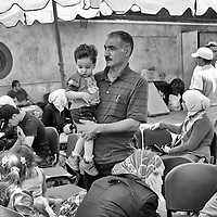 Egypt / Syrian refugees / A man holds his child as hundreds of Syrian refugees register for protection and other social services at UNHCR offices in the Zamalek neighborhood in Cairo, Egypt, Tuesday, May 28, 2013. Many Syrian refugees fled the violence in their homeland and were displaced to neighboring countries, including Egypt. The Ministry of Foreign Affairs estimates that there may be almost 150,000 Syrian refugees in Egypt, most of whom reside in the cities of Cairo and Alexandria.  / UNHCR / Shawn Baldwin / May 2013