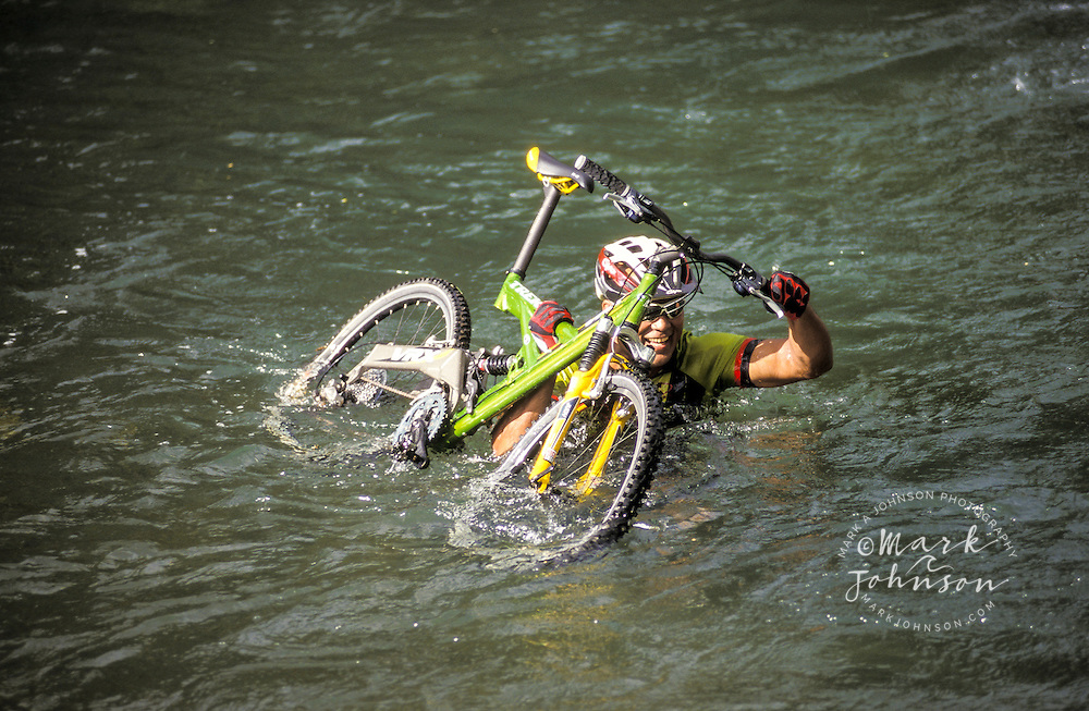 USA, Hawaii, Kauai, man carrying mountain bike through stream.  MR available