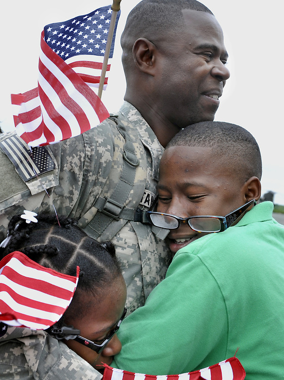 Staff Sgt. Guido Constant, of Norwalk, is hugged by his daughter Lunise, left, and son Kendrick at the Army aviation support facility in Windsor Locks, Conn. About 110 soldiers of the 250th Engineer Co., Connecticut National Guard who were deployed to Iraq last winter have returned home. (AP Photo/Jessica Hill)
